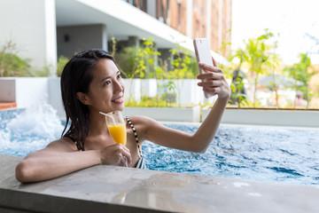 Beautiful Woman in pool and enjoy juicy drink and taking selfie
