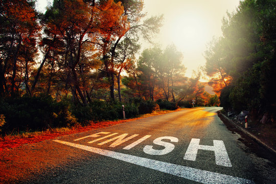 Sunset countryside asphalt road with finish line message on the floor.