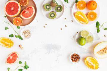 Poster Vruchten Colorful fresh fruit on white table. Orange, tangerine, lime, kiwi, grapefruit. Summer fruit. Flat lay, top view, copy space
