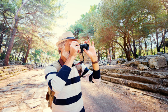 Enjoying travel. Senior man with backpack taking photo on camera on ancient sightseeing background.