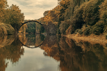 Autumn, cloudy evening over Devil's bridge in the park Kromlau, Germany.Stylized photo on old, retro, vintage
