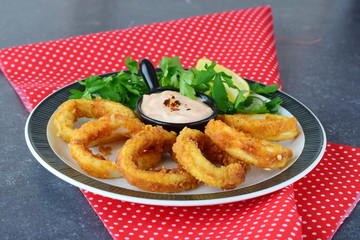 Calamary rings fried with spicy souce and rocca. Mediterranean lifestyle. Healthy food