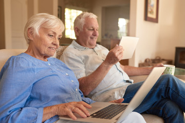 Content seniors browsing the internet from their living room sofa