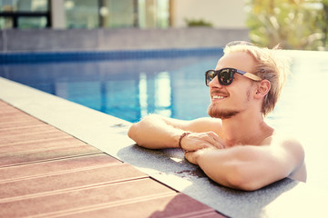 Vacation concept. Happy young man at swimming pool.