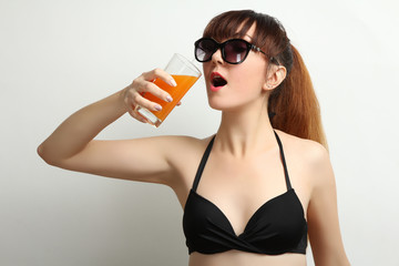 Woman with a cocktail in a swimsuit