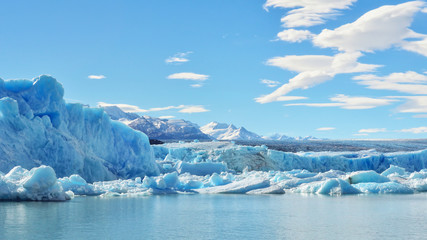 Single blue icebergs and blue sky with white clouds and mountains on the background. Upsala Glacier at Argentino Lake, Los Glaciares National Park, Patagonia, Argentina