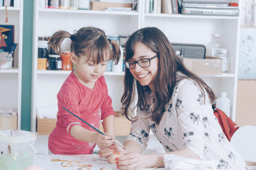 Smiling mother and daughter painting easter eggs at home