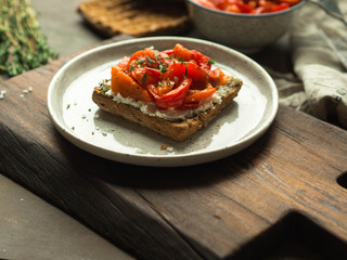 Vegetarian toast with baked pepper and cream cheese on a plate on a wooden board
