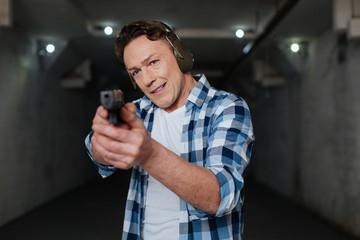 Handsome nice marksman holding a handgun