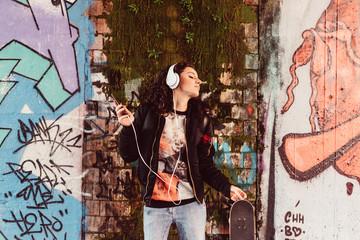 Young woman listening music dancing