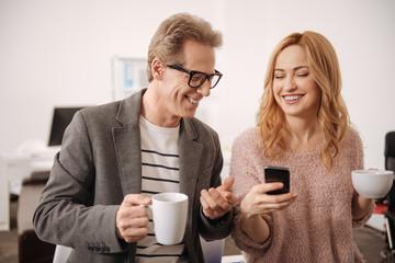 Happy colleagues enjoying coffee break in the office