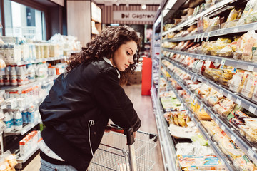 Woman pushing shopping cart at supermarket