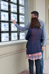 couple looks at the window of a real estate agency in the street