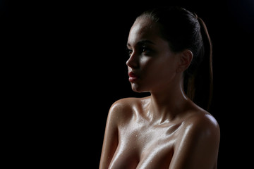 Beautiful girl with a nude make-up and wet hair and skin. Beauty face. Photo taken in the studio on a black background.