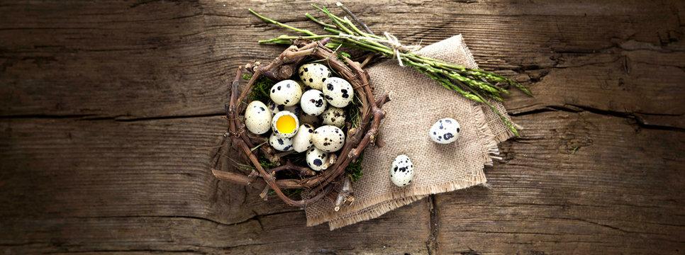 Uova di quaglia nel nido su sfondo di legno.