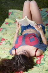 Smiling beautiful young woman lying on grass and reading book, against background of summer green park