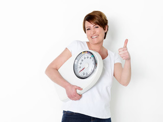 Girl with scale is proud to lose weight