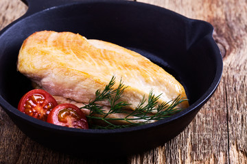 Fried chicken breast on skillet with tomatoes