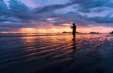Silhouette, man taking a picture with a smartphone on the beach and wonderful sky at sunset. Andaman seaThailand