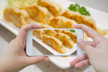 taking photo of Gyoza dumplings with smartphone