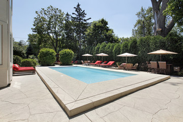 Swimming pool with red lounge chairs