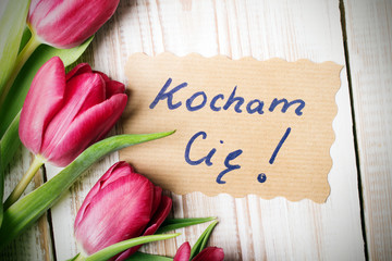 Polish word LOVE and bouquet of tulips on wooden background