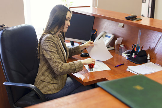 The woman puts a stamp to the document on the desktop. The work in the office