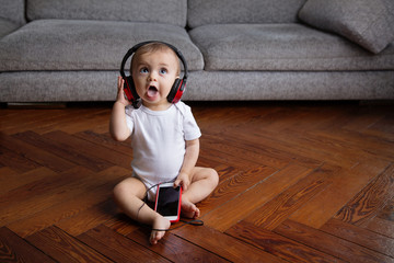 Sitting baby with headphones listening to music