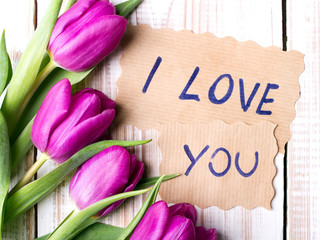 words I LOVE YOU and bouquet of tulips on wooden background