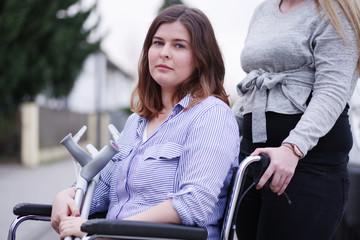 junge Frau wird im Rollstuhl geschoben