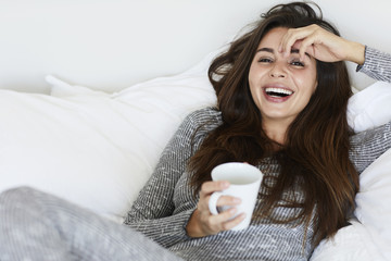 Beautiful woman laughing in bed, portrait