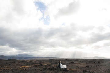 Married couple standing close to one another under cloudy sky of Iceland