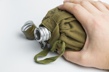 Hand holding military flask on white background.