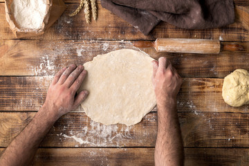Wall Mural - Man prepares the dough for cooking pizza on wooden table