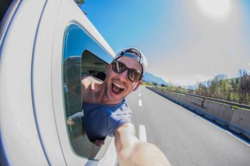 Handsome man taking a selfie on the road at van trip