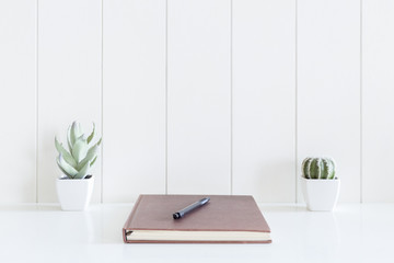 Notebooks diary and pen with cactus flowers vase on white desk and wooden background with copy space