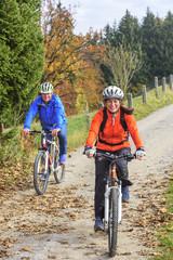 gutgelauntes Paar beim Radfahren im Herbst