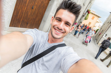 Handsome man taking a selfie in a urban scene smiling at the camera