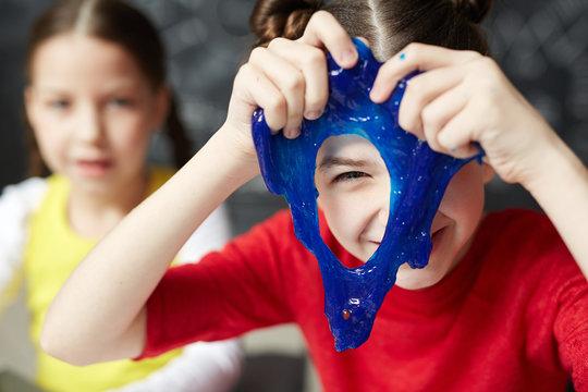Happy kid looking through hole in blue slime