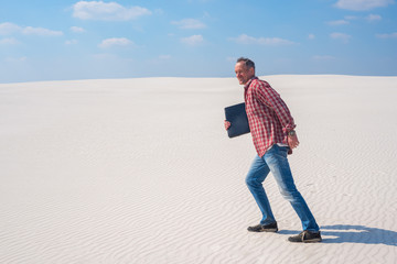 Joyful man is walking through the desert with a laptop in his hands