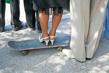Cropped image of Female Legs in white elegant shoes stand on a black skateboard and male legs next