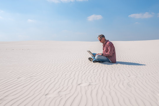 Man is passionate about work, with a laptop sits in desert