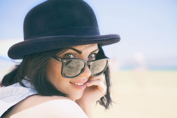 Portrait of smiling beautiful young woman in black hat and retro sunglasses on the beach