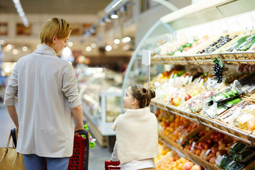 Woman and her daughter talking while moving along supermarket aisle
