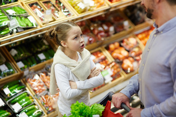 Little daughter asking her father for something in supermarket