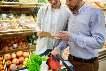 Young husband and wife discussing shopping list in supermarket