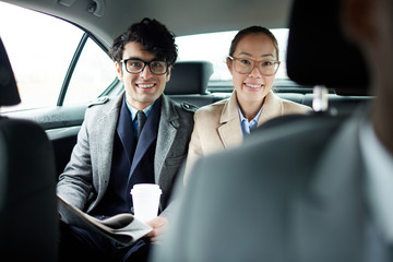Portrait of two successful business people riding on backseat of taxi: smiling cheerfully and looking at camera on the way to work