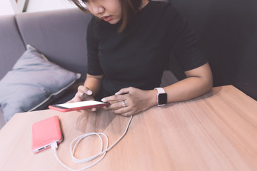 Woman holding a smart phone and a charger. Powerbank and smartphone in girl's hands. Energy charger power bank smart phone. Still life modern digital concept.