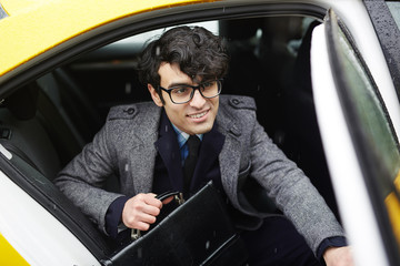 Portrait of young smiling  Middle-Eastern businessman with briefcase getting out of taxi to rainy autumn street