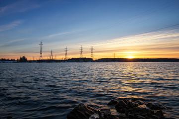 линии электропередач на берегу водохранилища на закате дня